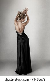 Young blond woman in open-back black elegant dress