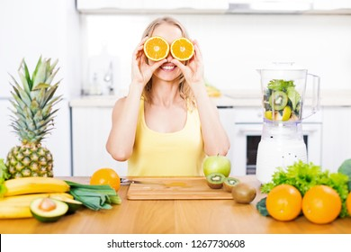 Young blond woman with orange over eyes, smiling and preparing detox fruits smoothie in blender on white kitchen, healthy eating, cooking, dieting concept