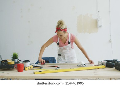Young blond woman in pink shirt and white overalls with tape measure bending over wooden workbench with tools checking length of plank on background of white unpainted wall .
