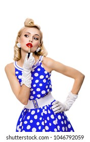 Young blond woman in pin-up style blue dress in polka dot, applying lipstick, isolated over white background. Caucasian model posing in retro fashion and vintage concept.