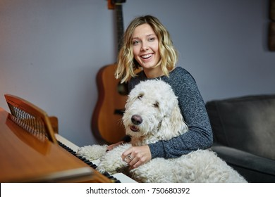 young blond woman playing piano with goldendoodle