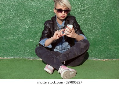 young blond woman with punk style hair using her mobile phone and leaning on green wall