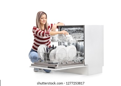 Young blond woman putting a cup into a dishwasher isolated on white background