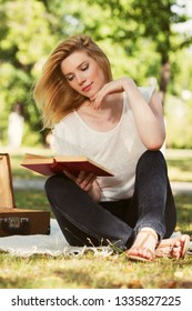 Young blond woman reading a book in city park  Stylish fashion model in white t-shirt and black jeans
