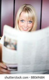 young blond woman reads a newspaper/woman with a newspaper