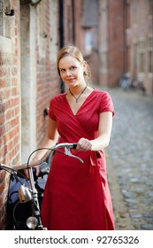 Young blond woman in red dress standing on a street with old bicycle