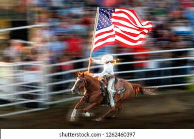 A young blond  woman riding a galloping horse with an American flag waving with motion blur