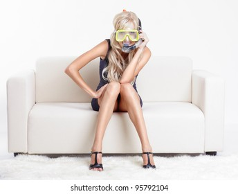 young blond woman in scuba mask on couch with white furs on floor