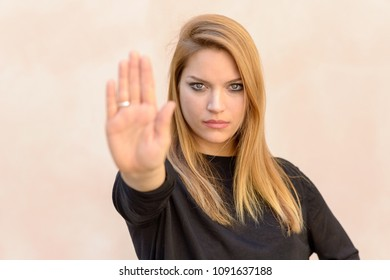Young blond woman showing hand stop gesture against neutral background