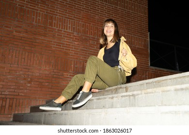 Young blond woman sitting on staircase outdoors in the city at night