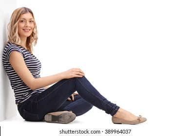 Young blond woman sitting on the floor and looking at the camera isolated on white background