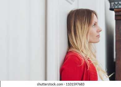 Young blond woman standing leaning against a white interior wall daydreaming looking up with a serious expression, with copy space