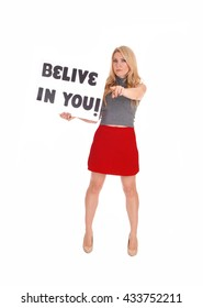 A young blond woman standing in a red skirt and gray sweater holding 