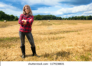 Young blond woman stands proud with rubber boots in a field of straw