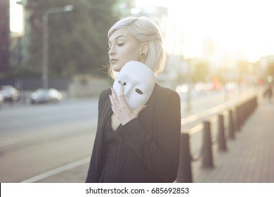 Young blond woman taking off a mask. Pretending to be someone else concept. outdoors on sunset.