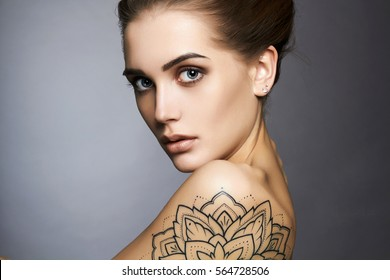 Young blond woman with tattoo.Beautiful blonde Girl with make-up.fashion portrait