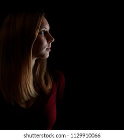 Young blond woman thoughtfully looks to the side against a dark background