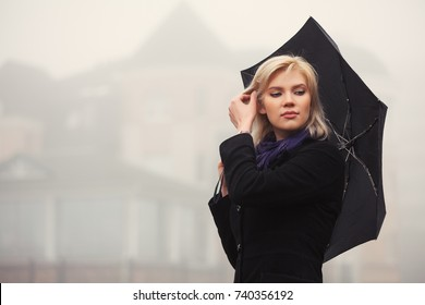 Young blond woman with umbrella walking in a fog. Stylish fashion model in classic black coat outdoor