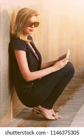 Young blond woman using tablet computer in city street Stylish fashion model in sunglasses