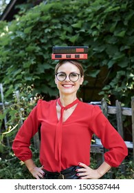 Young blond woman, wearing red shirt and eyeglasses, holding two books on her head. Student with black and red books, smiling. Studying fun. Pretty girl, balancing with books on her head,