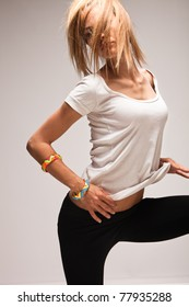 young blond woman in white t-shirt dancing, studio shot
