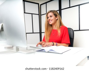 young blond woman working happily in the office with computer and mobile phone