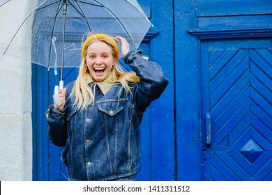 Young blond woman in yellow hat jeans jacket under transparent umbrella. Model in hipster sport clothes over blue wall outdoor. Positive teenager girl with fly, airy hair toothy smile going crazy
