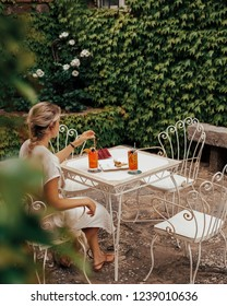 Young blond women outdoor stirring with paper straws spritz cocktail, drink made with Aperol, Prosecco & soda. Patio Garden greens on walls in Tuscany Italian countryside. Classy outdoor metal chairs.