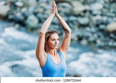 young blond yoga woman in blue dress suit stands in Vrikshasana pose with her eyes closed and enjoys the sounds of nature while standing by mountain stream on warm summer day. Unity with nature