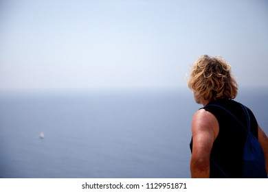Young blonde adult man dressed in summer style with a black tshirt looks out over the sea horizon from a clifftop