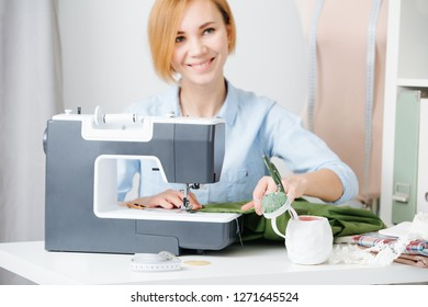 Young blonde attractive needlewoman at cozy small studio working with sewing machine. She dressed modestly for work, wearing blue shirt. Smiling, posing, distracted. Guiding fabric.