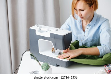 Young blonde attractive needlewoman at cozy small studio working with sewing machine. She dressed modestly for work, wearing blue shirt. Guiding fabric.