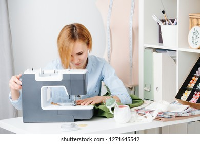 Young blonde attractive needlewoman at cozy small studio working with sewing machine. She dressed modestly for work, wearing blue shirt. Focused. Guiding fabric.