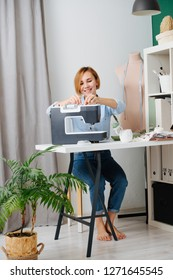 Young blonde attractive needlewoman at cozy small studio working with sewing machine. She dressed modestly for work, wearing jeans and blue shirt. Bare footed. Habit. Full length. Vertical.