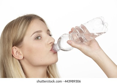 A young blonde attractive woman drinks mineral water out of a plastic bottle.