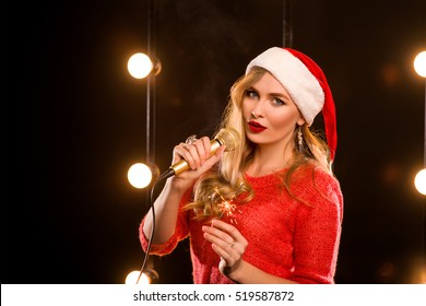 young blonde attractive woman in red sweater and red new year hat with microphone and sparkler on stage