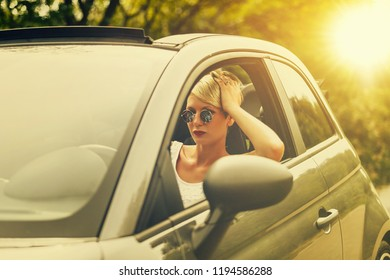 Young blonde attractive woman smiling and looking straight while driving a car.