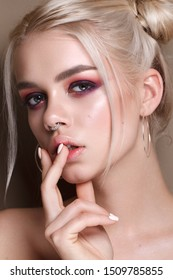 Young blonde beautiful girl with the colorfull make-up, bunches hairstyle, red and lilac smoky eyes. Septum piercing, silver accessories.
