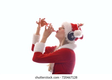 A young blonde beautiful girl wears a Santa Claus suit and has headphones on her head. She enjoys listening to the Christmas carols she hears on the radio.