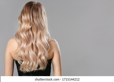 Young blonde with beautiful hair on grey background