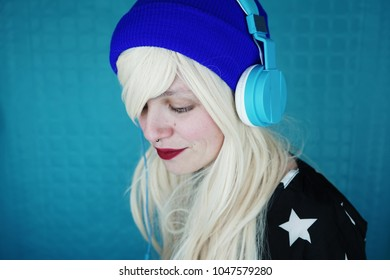 Young blonde and beautiful woman listening to music with her headphones
