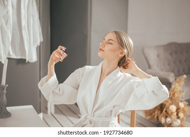 Young blonde beautiful woman in the white bathrobe sitting next to the table and using perfume bottle. Light morning at home with beautiful modern interior