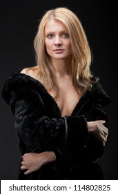 the young blonde in a black fur coat