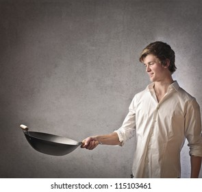 Young blonde boy cooking with a pan