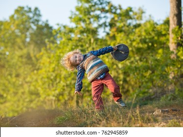 Young blonde boy with long curly hair playing in outdoor in autumnal forest.