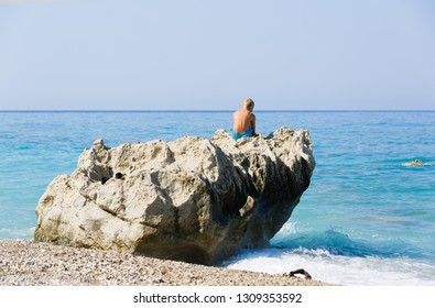 Young blonde boy sits on a huge coastal rock next to the blue sea, Greece.