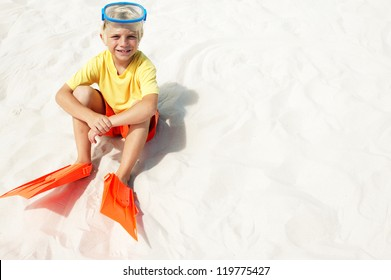Young blonde boy sitting in white beach sand wearing his flippers and goggles as he waits to go swimming in the sea with copyspace