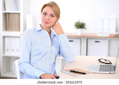 Young blonde business woman with laptop in the office. Business concept.
