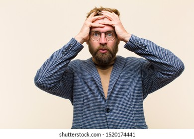 young blonde businessman feeling horrified and shocked, raising hands to head and panicking at a mistake