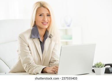 A young blonde businesswoman, elegantly dressed sitting at a desk in front of laptop in her office with a smile on her face looking at the camera.